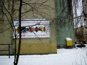 Plakat wyłania się zza drzew. Fot. BG